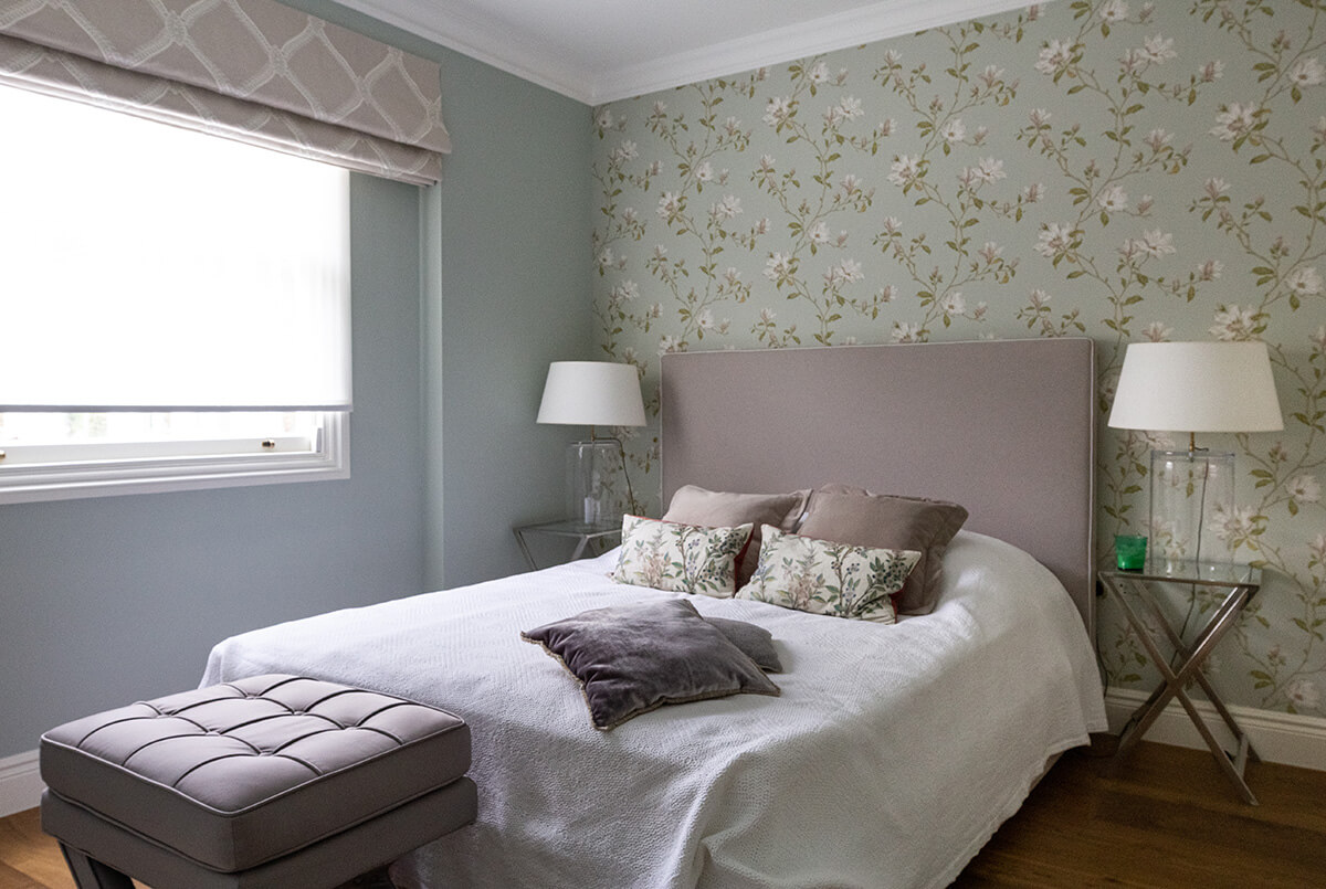 residential interior design for elegant bedroom with floral wallpaper, grey roller blinds and cosy bed in victorian style in St John's wood, London
