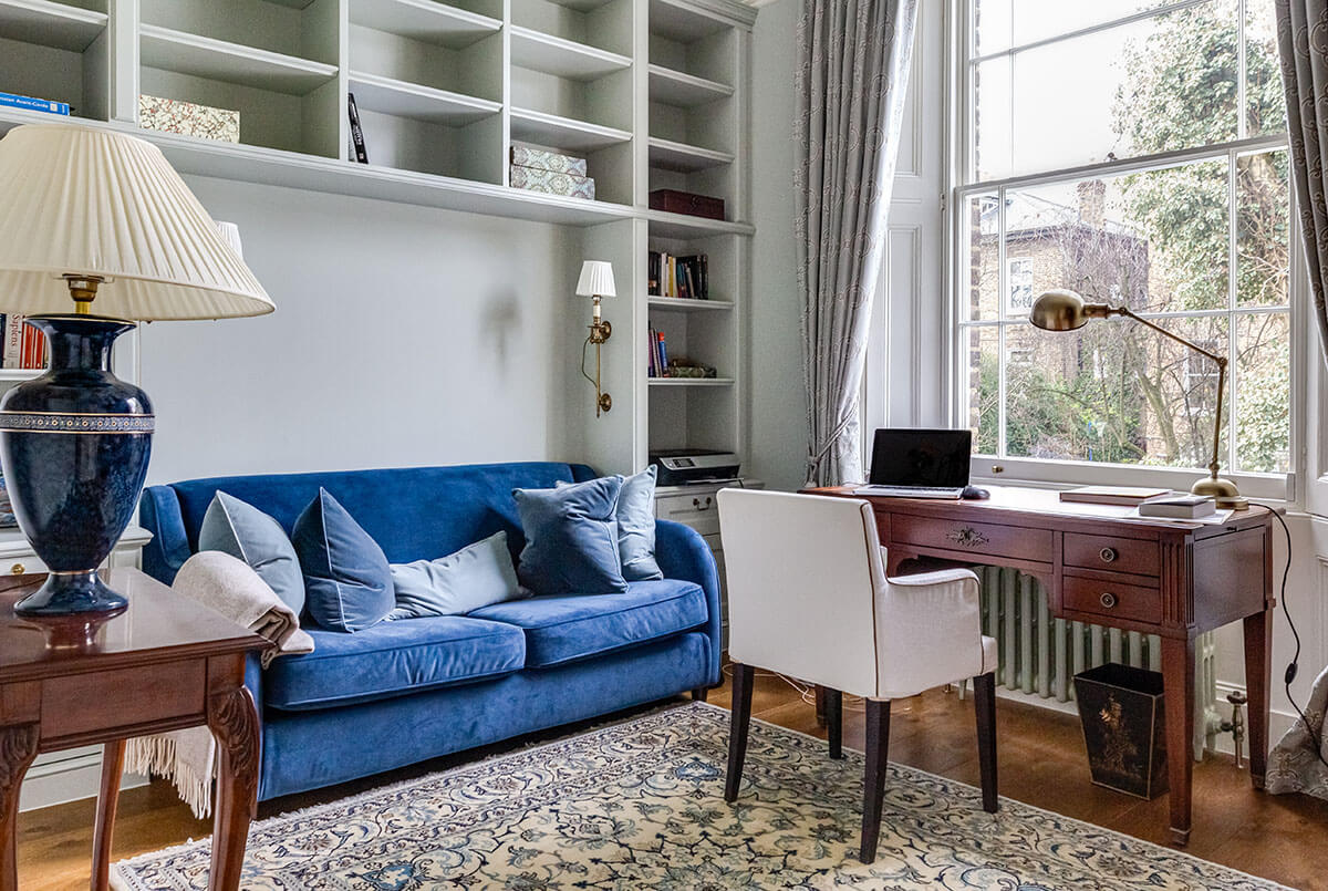 residential interior design for home office with soft green bookshelves, blue sofa and antique desk in Grade II listed house in St John's Wood, London