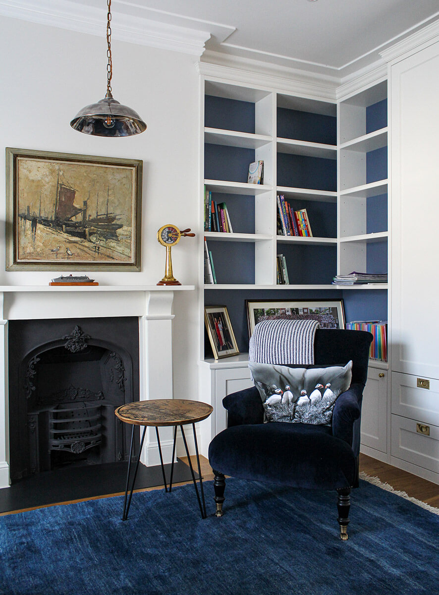 residential interior design for a room with bright blue carpet, blue armchair, fireplace and white build in bookshelf in Grdae II listed House in St John's Wood, London