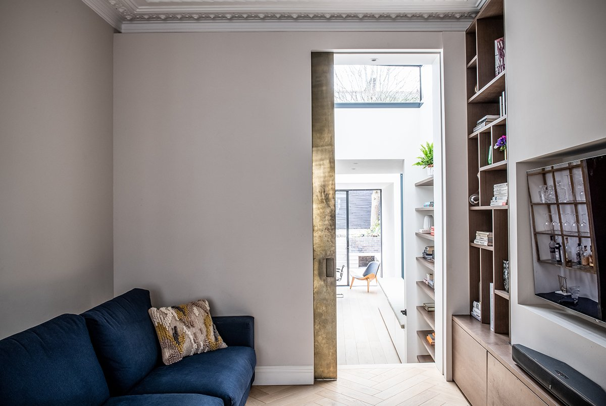 residential interior design for a small yet practical room with custom made TV reception unit and cosy blue sofa in Bromley, London