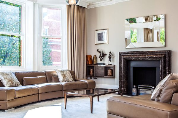luxury interior design for a grand and spacious reception room with fireplace, high quolity furnitureand floor to ceiling windows in Kensington, London