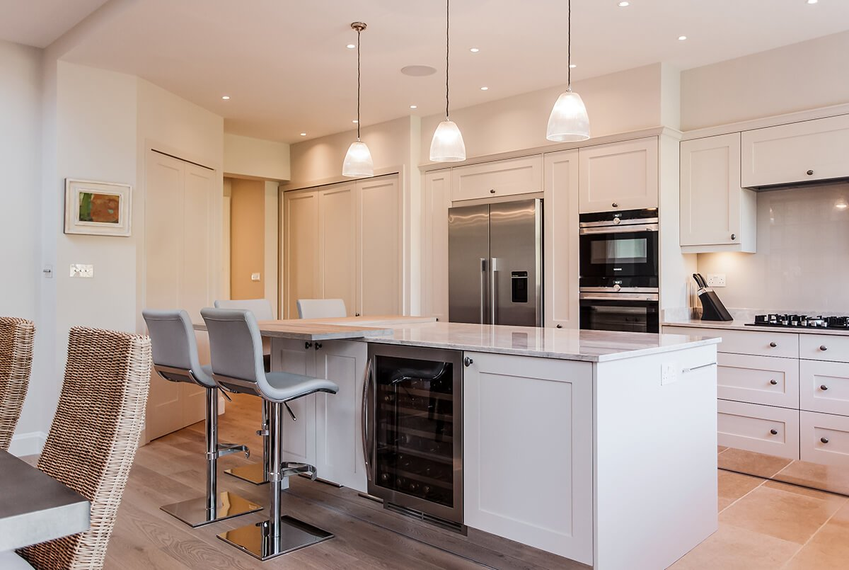 residential interior design for a traditional kitchen with bespoke neutral cabinets, wicker furniture, dining area, Wandsworth, London