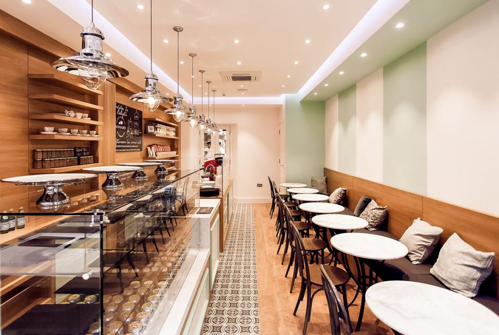 Fully refurbished industrial style cafe with bespoke joinery, glass display and chrome pendant lights in Battersea, London