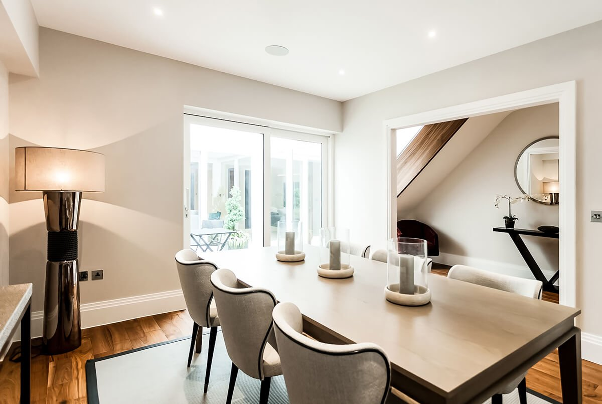 residential interior design for a dining room with light walls, white comfortable chairs and floor to ceiling windows in Battersea, london