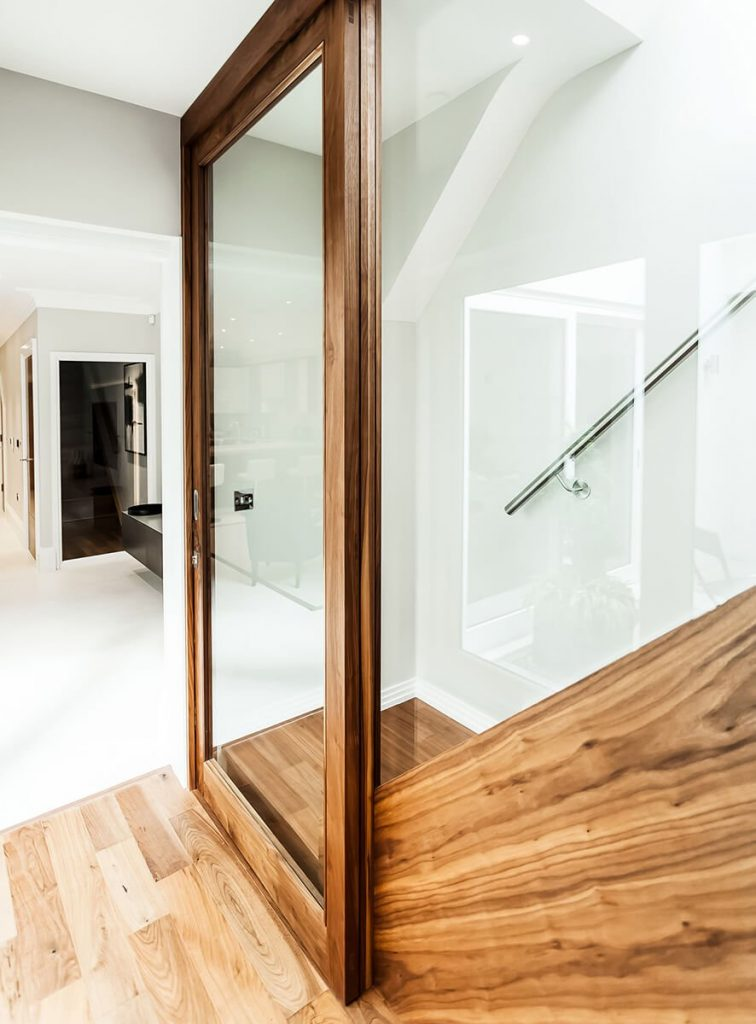 Wood staircase with a steel handrail and glass partition door