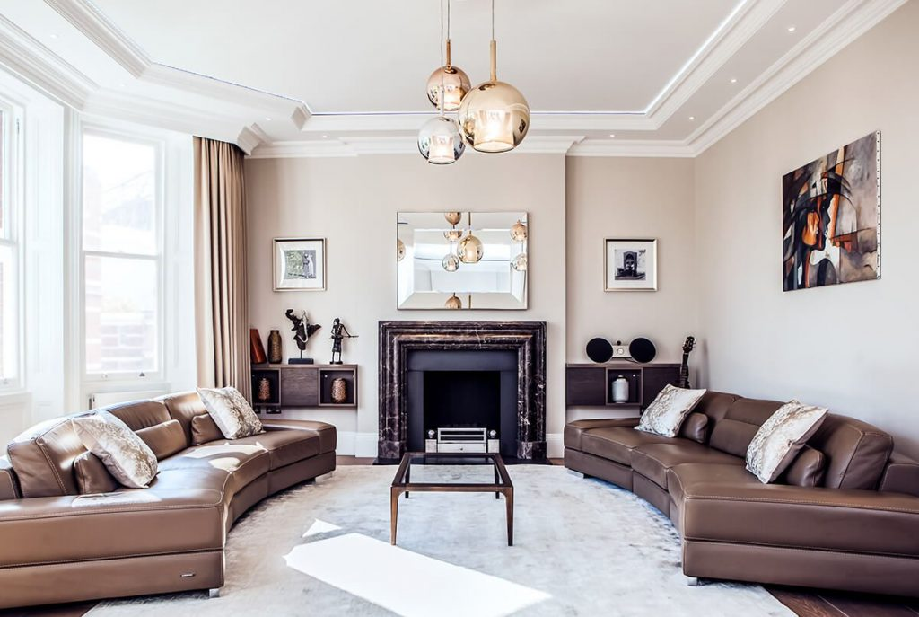 A spacious light luxurious reception room with leather sofas and a grand marble fireplace in Kensington, London