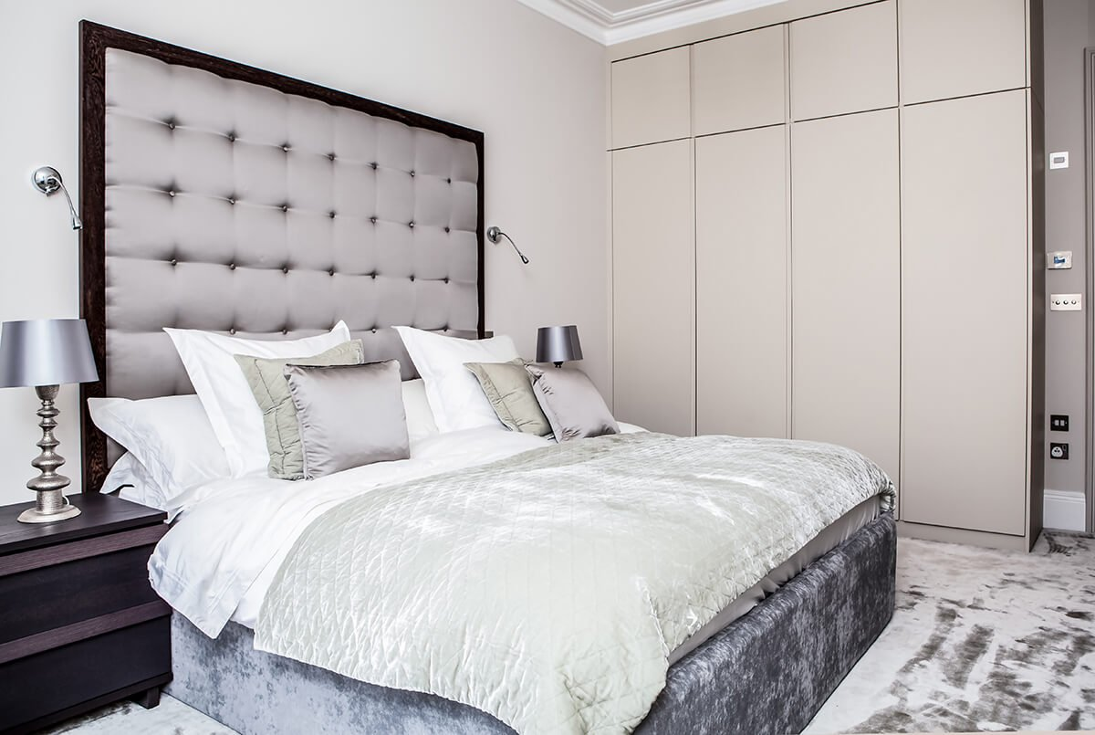 residential interior design for a luxury master bedroom in light grey hues with large bay windows, grey carpet and comfortable bed, Kensington, London