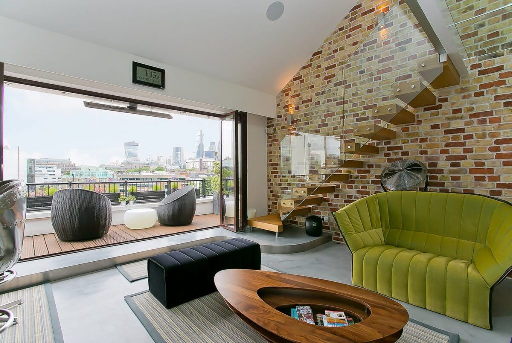 interior design for modern loft apartment. large, bespoke kitchen in open plan design with exposed brick walls and glass mezzanine level in Wapping, London