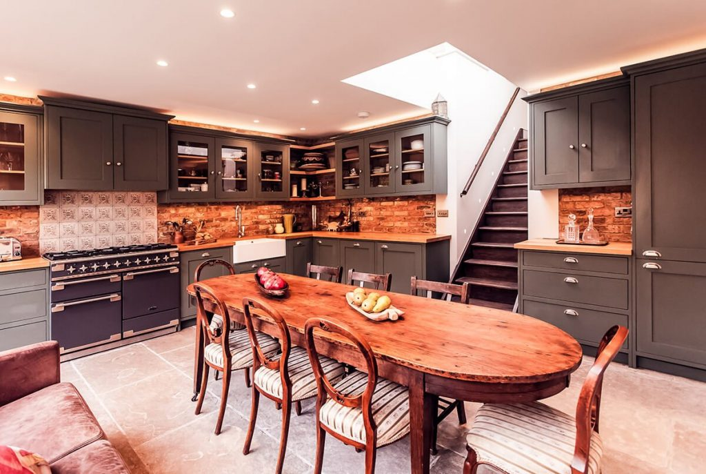 residential interior design for spacious kitchen in Victorian Style with brick walls, soft green bospoke cabinets, dining area in Shepherd's Bush, London