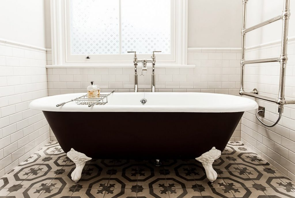 dreamy bathroom with free standing bath on feet, tiled flooring and walls in London