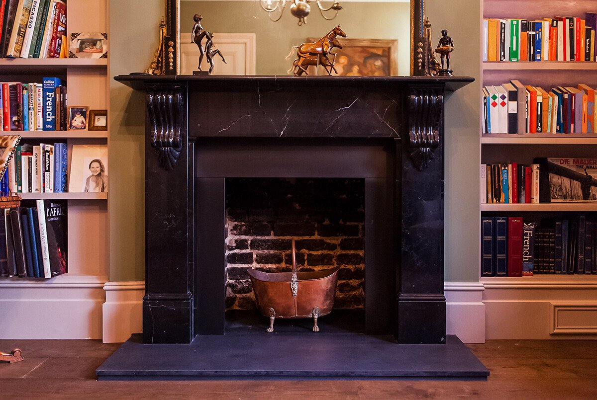 residential interiro design for a dreamy livingroom in Victorian style with cosy velvet furniture, black fireplace, bookcase in Shepherd's Bush, London