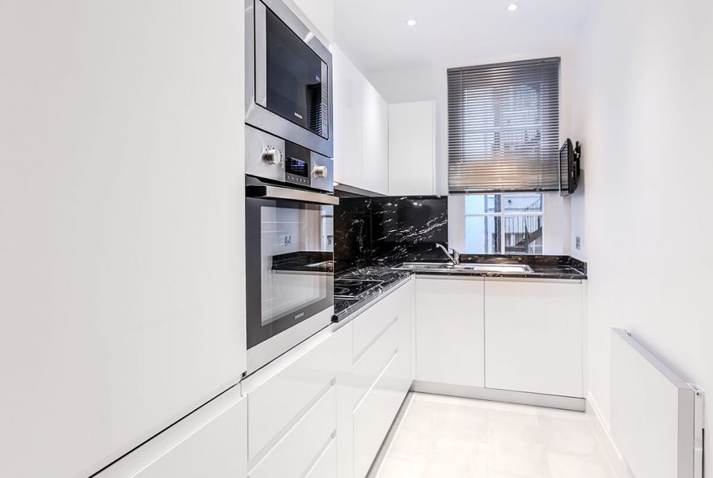 small yet practical kitchen with bespoke white cabinets, blak marble worktop in Mayfair, London