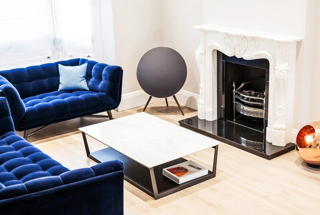 A contemporary reception room with signature white fireplace, blue velvet designer furniture and rosegold lamp in Chelsea, London