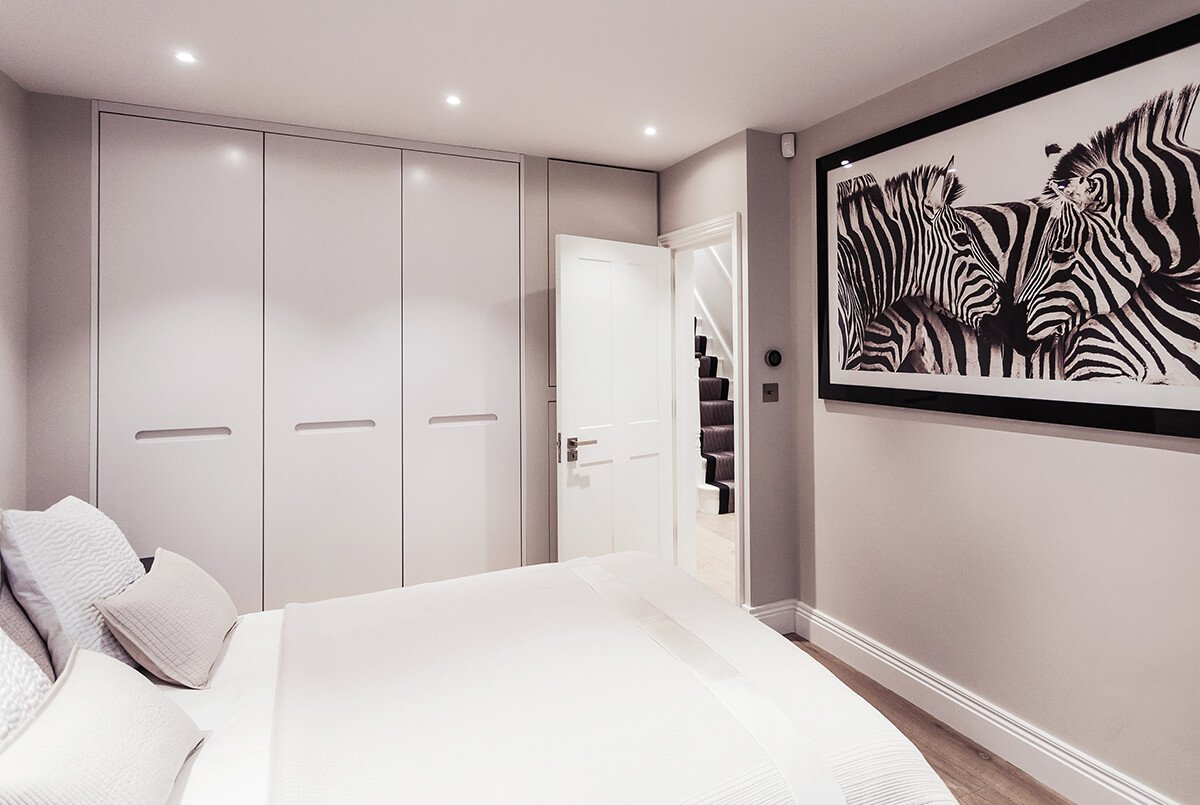 Fully renovated bedroom in minimalist style with wooden flooring, bespoke built in storage