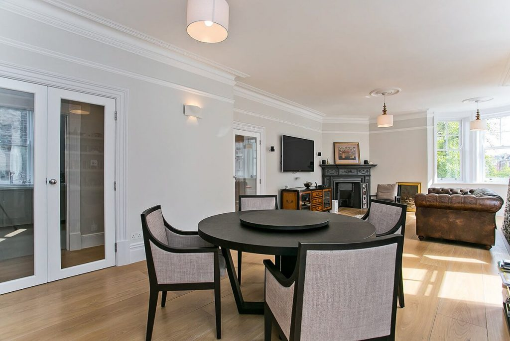 Open plan dining room and living room with dining area, bookshelves and fireplace in Marylebone, London