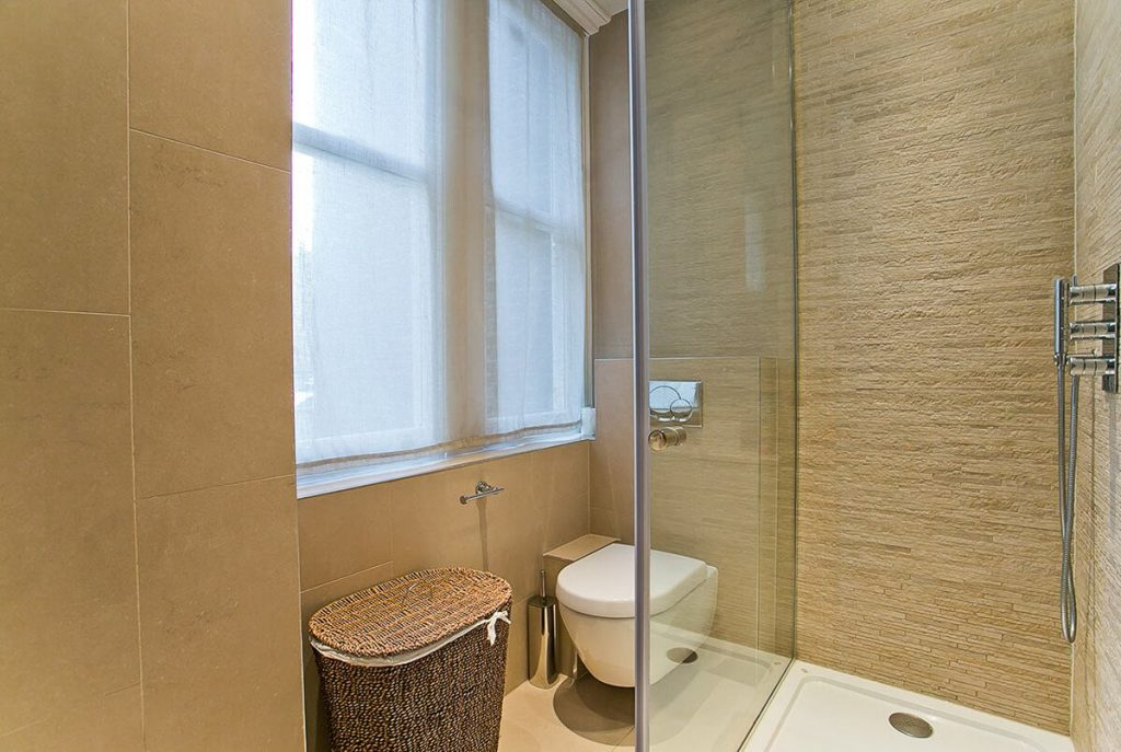 small and elegant bathroom with tiled walls and floor in Marylebone, LOndon