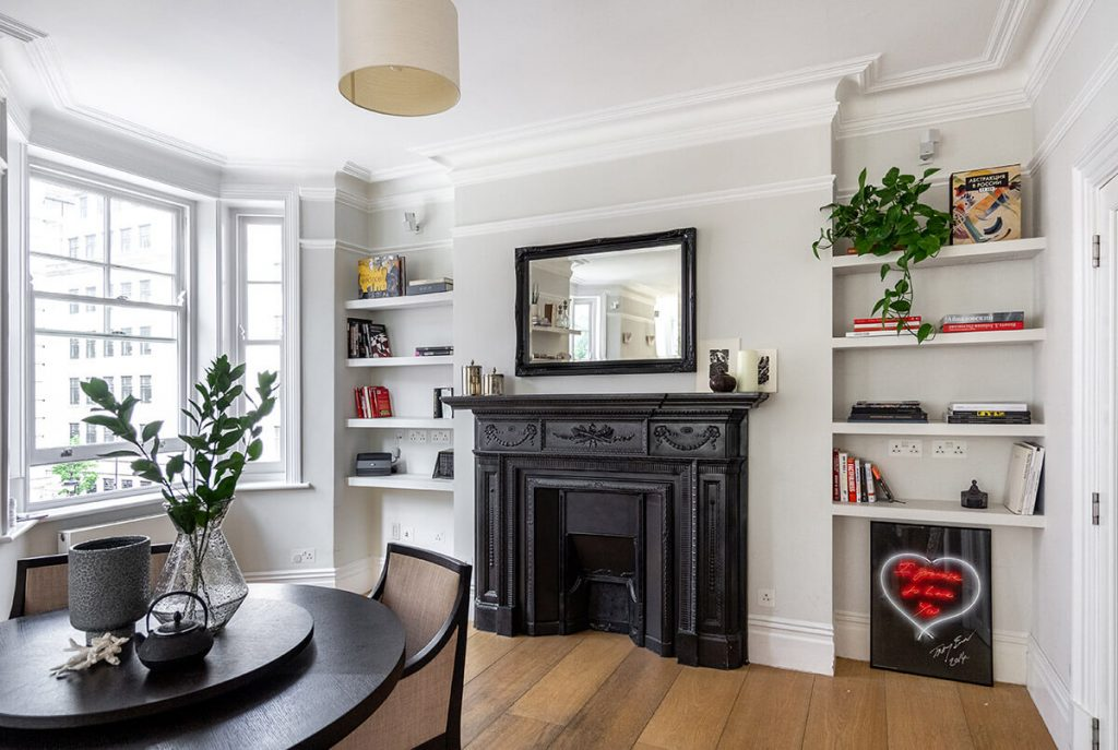 Open space for dining room and living room with dining area, bookshelves and fireplace in Marylebone, London