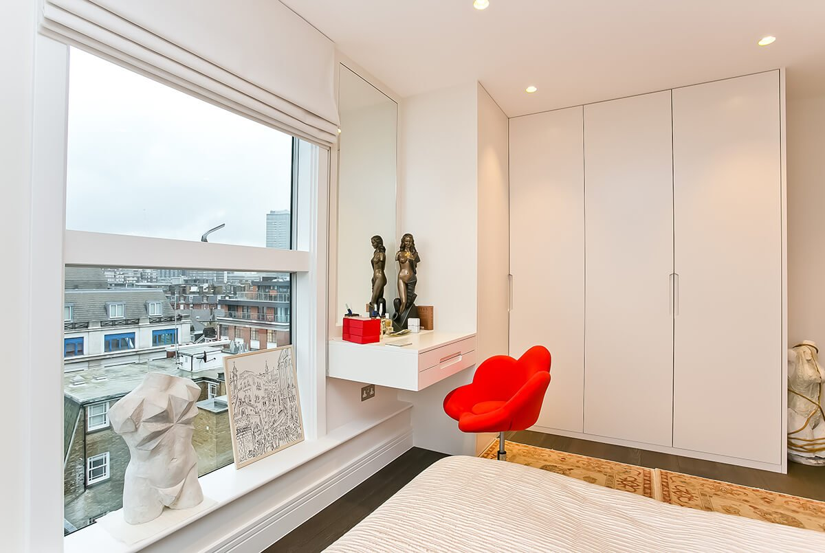 residential interior design for light and cosy bedroom with bright red accents, large windows in westminster, London