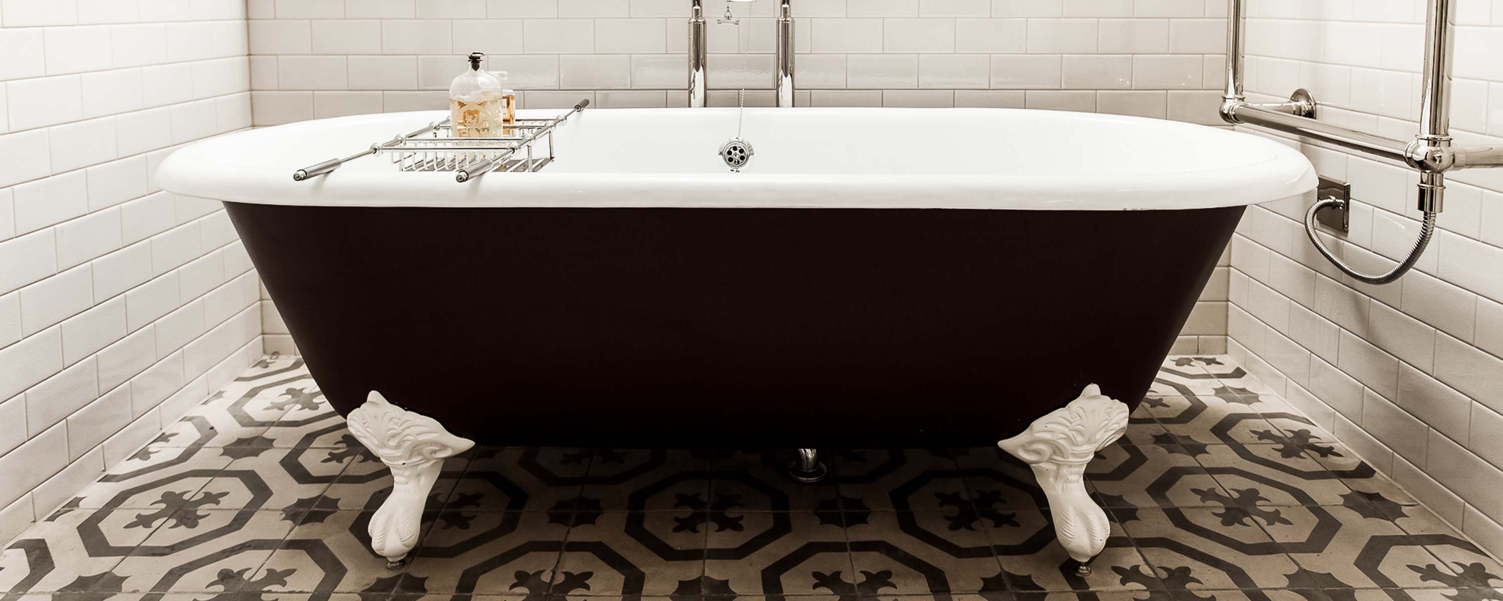dreamy bathroom with free standing bath on feet, tiled flooring and walls