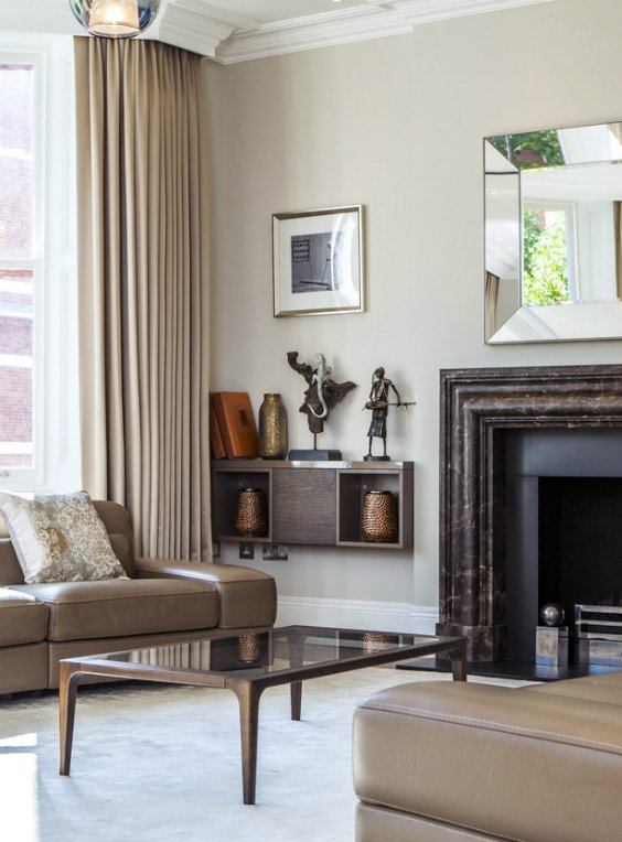 luxury and modern interior design for grand and spacious reception rooom with marble fireplace, designers fcomfortable furniture, floor to ceiling windowns and sand colour curtains in Kensington, lONDON