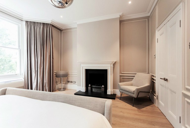 grand and spacious interior design for elegant master bedroom in neutral colours with firepalce, large windows, sand colour curtains in Chelsea LOndon