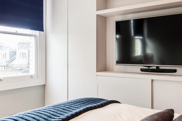 interior design for small yet practical bedroom with built in storage and deep blue roller blinds, London
