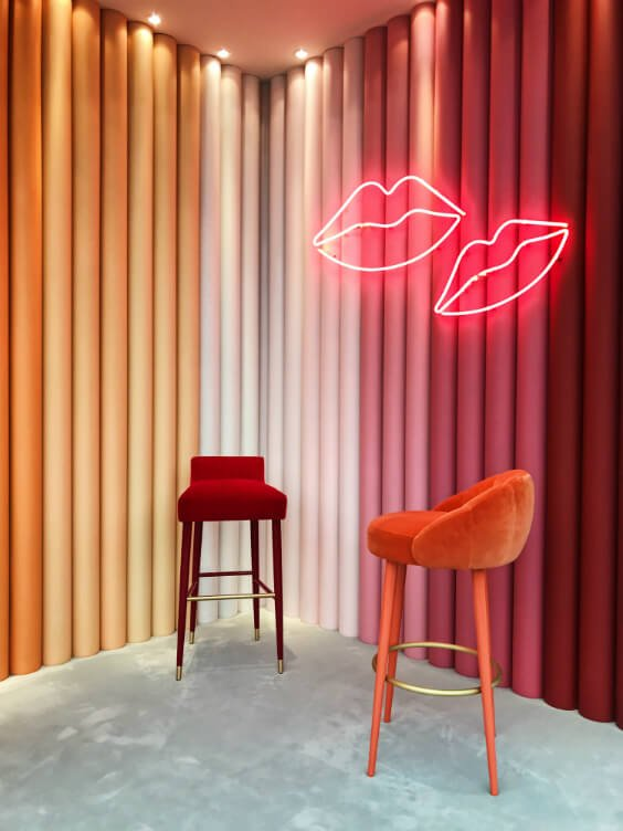 gradient wall from orange to red wih neon lips and comfy velvet high chairs