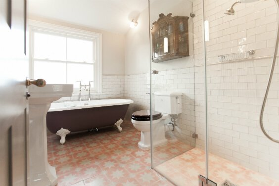 interior design for a bathroom in victorian style with free standing bath on the feet, tiled flooring, glass shower stall, London
