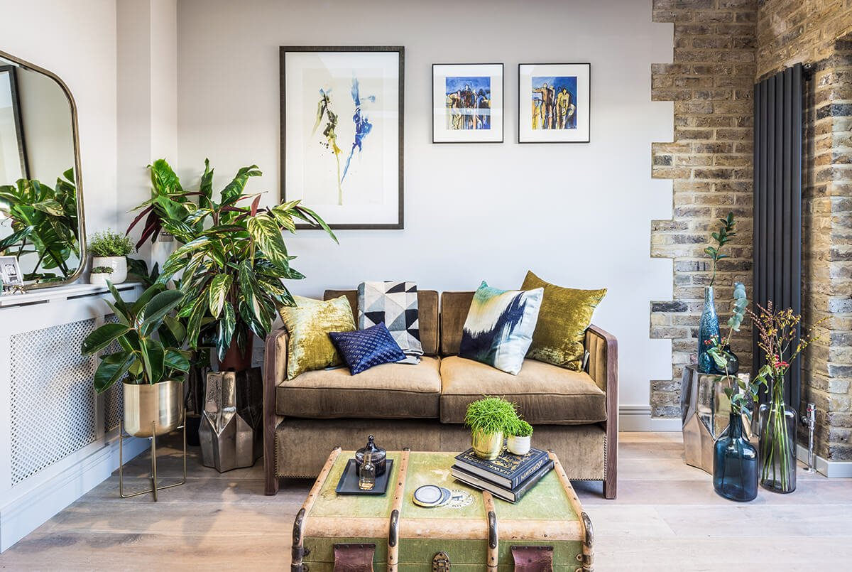 residential interior design for open plan living room and kitchen in eclectic style with designer leather chairs and bright blue and yellow cusions in Bentworth Road, London