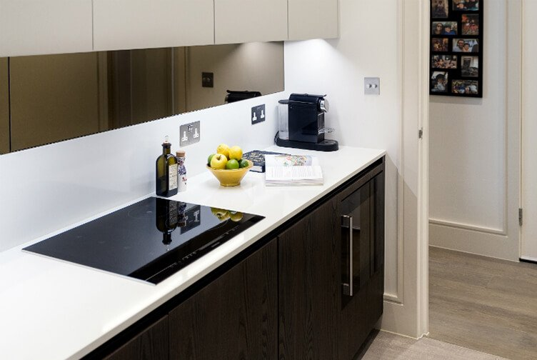 Completely renovated contemporary and elegant kitchen with stone top and tinted glass splashback