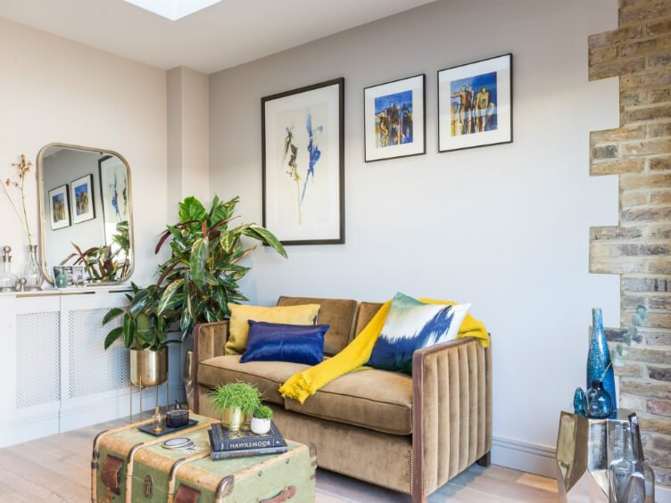 Eclectic sitting room interior with khaki velvet sofa, antique chest table, yellow, blue and silver accessories and plants.
