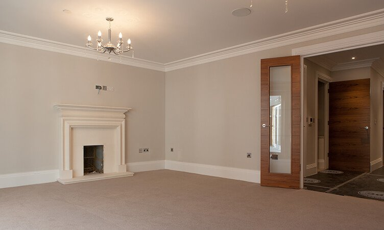 Unfinished before look of a spacious reception room with grand fireplace and wood glass door.