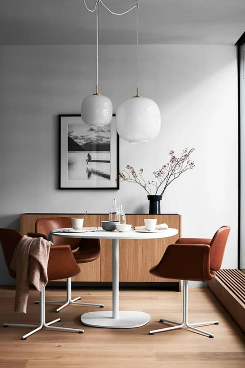 Sophisticated and delicate cosy Scandinavian dining area interior with two white suspended pendants and brown leather chairs.