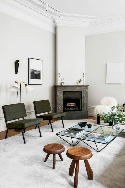 -Sophisticated and elegant cosy Scandinavian style sitting room interior with glass coffee table, green armchairs and marble fireplace.