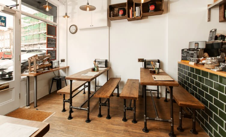 Compact and practical industrial style café in Battersea, London, with diy wooden tables and green metro tiles bar.