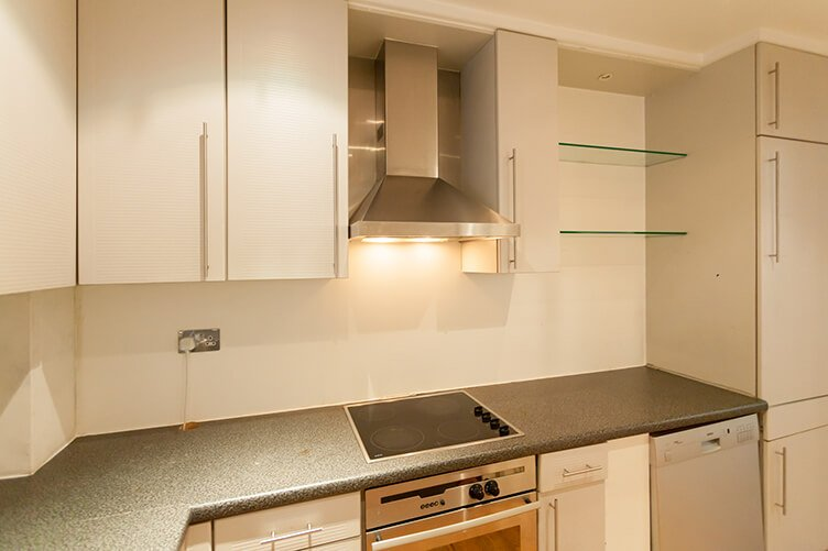 Before image of a white modern look kitchen with exposed extractor fan