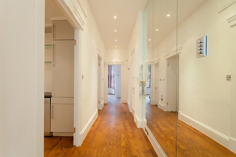 Before image of a contemporary look hallway with wooden flooring, mirrored built in storage unit and downlights