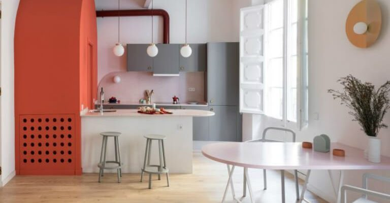 interior design for a spacious kitchen with pink painted walls, bright bespoke cabinets, dining area