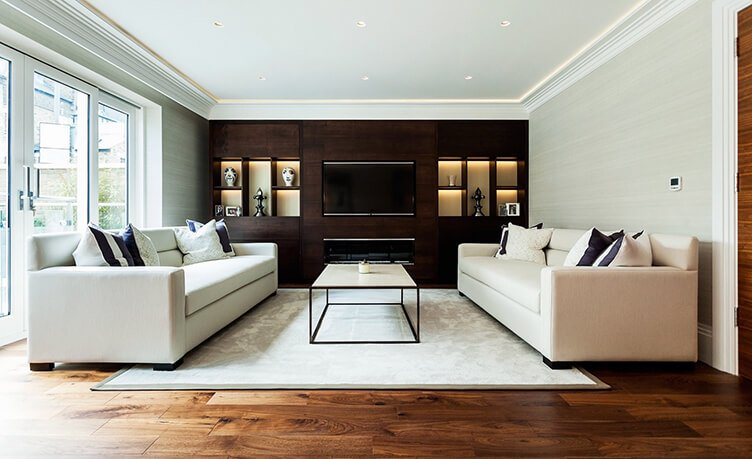 Perspective view of light, spacious, neutral living room space with bespoke joinery unit in dark wood veneer