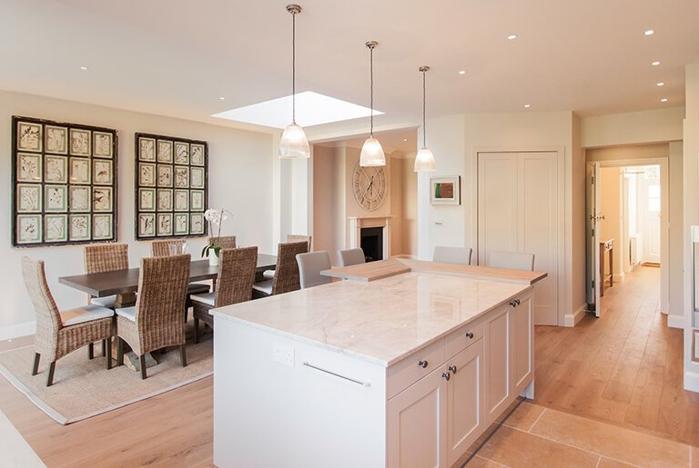 Spacious, light, neutral palette open plan kitchen interior with grand kitchen island and ceiling skylight.