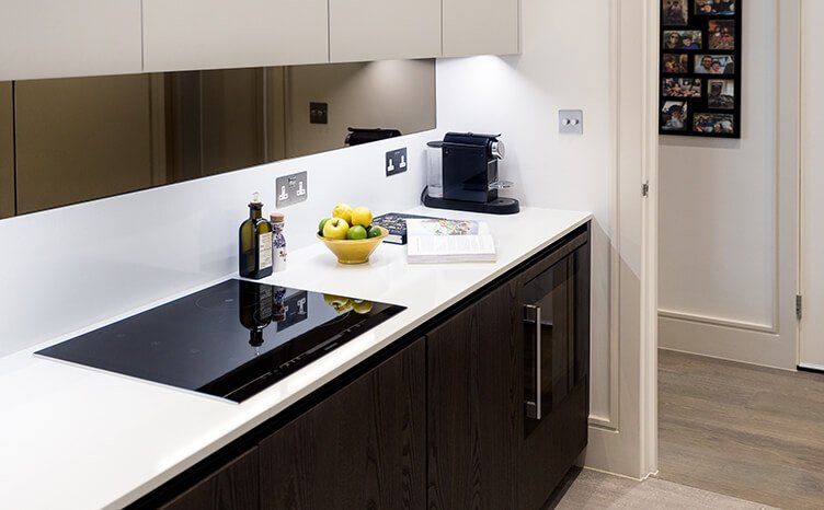 Sleek, minimalistic dark kitchen cabinets with light stone worktop and tinted glass splashback