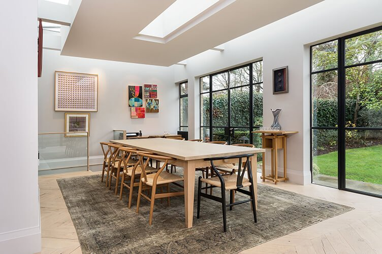 Spacious light dining room with wooden floor and a persian rug