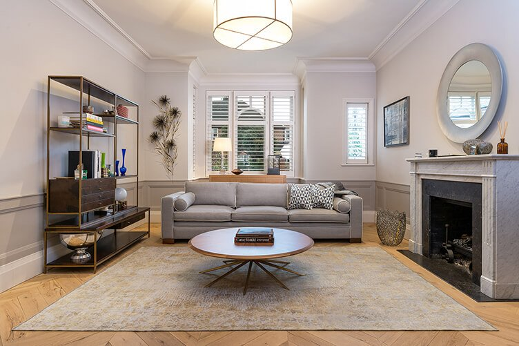 Grand cosy sitting room with wooden floor and persian overdryed rug and fireplace