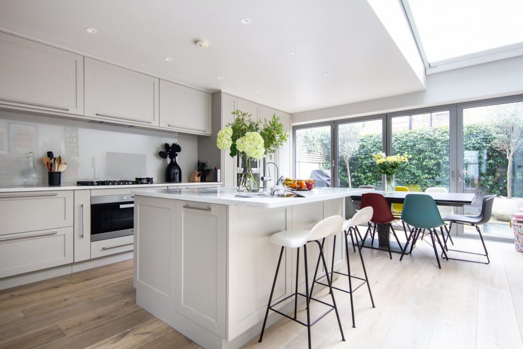 light and grand interior design for a kitchen with a dining area with custom made joinery, floor to ceiling windows