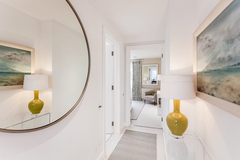 small light hallway with a larhe round mirror in Chelsea, London