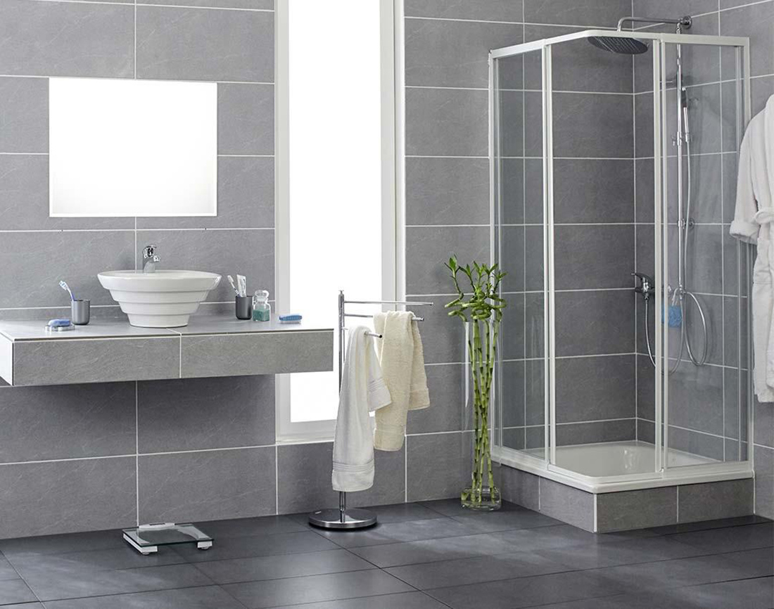 spacious bathroom with grey tiled flooring and walls, round mirror, shower cabin