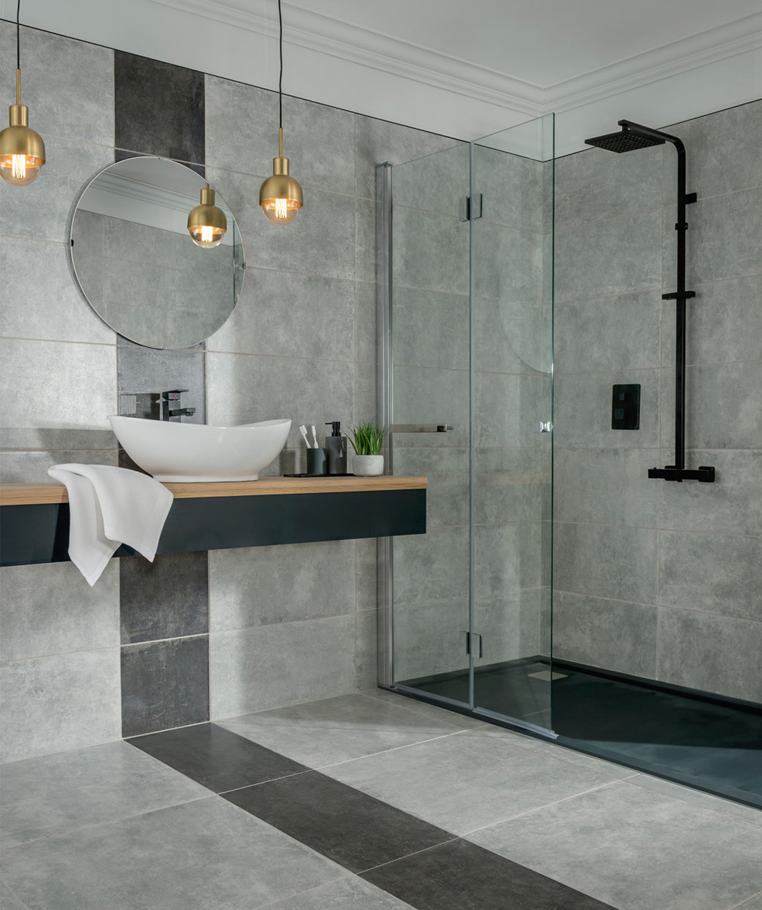 spacious bathroom with grey tiled flooring and walls, round mirror, shower