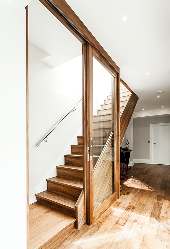 residential interior design with Custom made walnut stained planks matched perfectly to the floating staircase via using the same bespoke stain, London