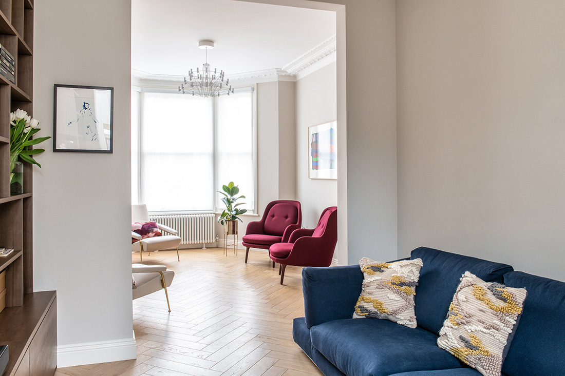 residential interior design for light and spacious receprion room with designer burgundy velvet armchairs, wooden flooring and Rubber plant in Bromley, London
