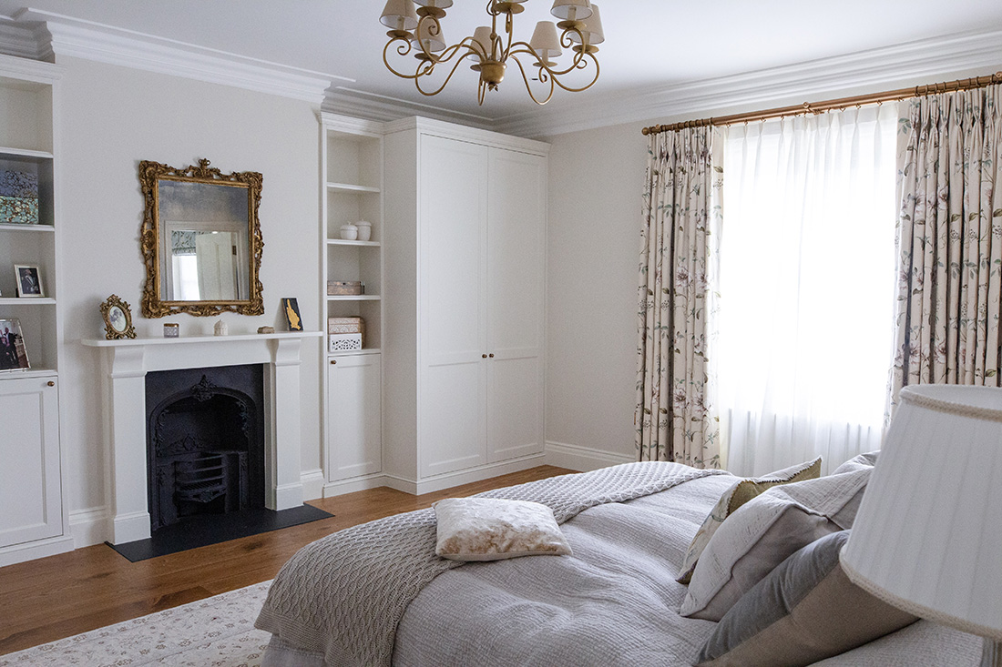 residential interior design for spacious master bedroom with white painted walls, built in storage, fireplace and antique mirror in Grade II listed House in St Johnswood, London